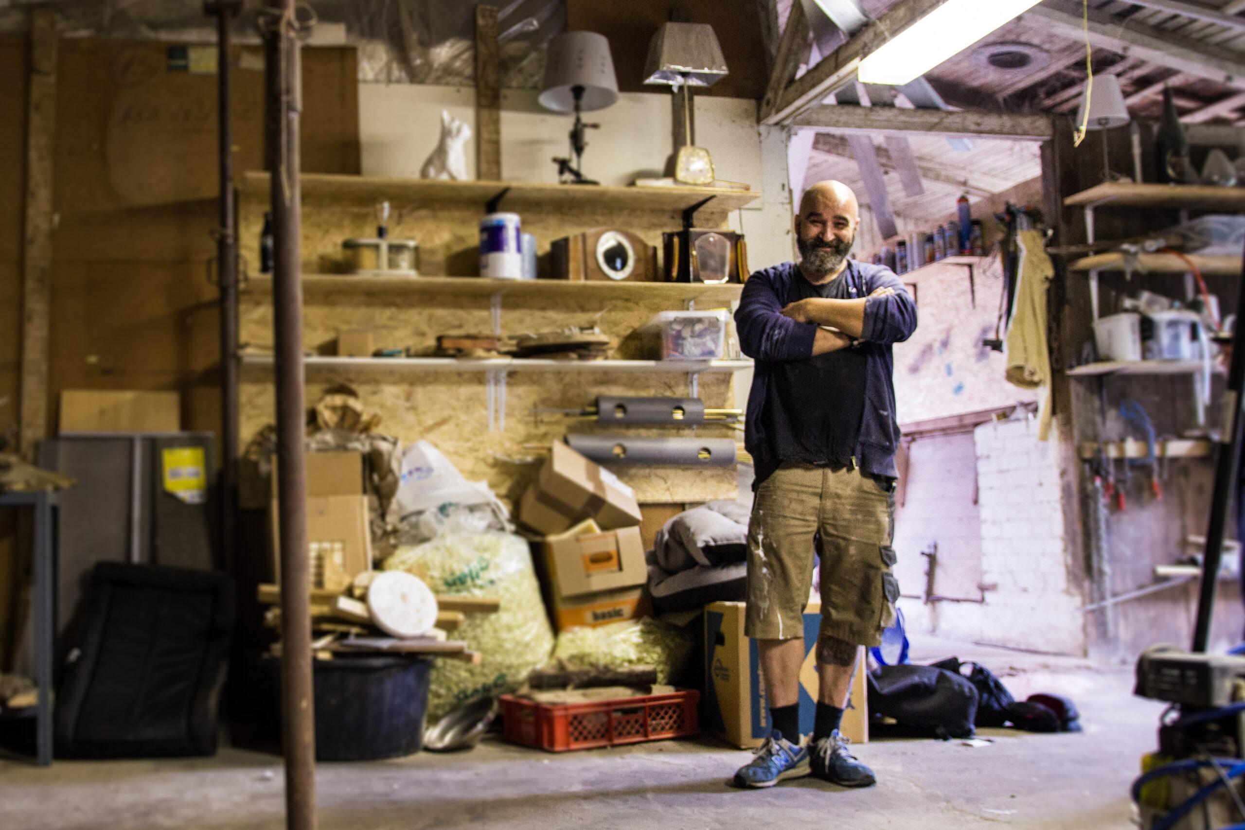 Hier seht ihr Norman Aksoy in seiner Werkstatt vor einem Ragl mit Lampen